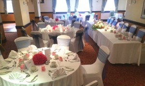 Savoy Suite top table on right facing round tables, dance floor in corner, blue sashes, pink rose centrepiece